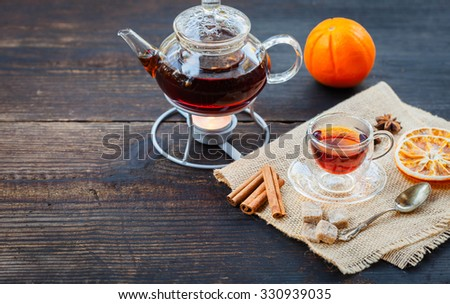 Hot orange Christmas tea on rustic wooden table - stock photo