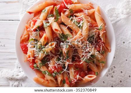 Hot pasta arrabbiata with parmesan and herbs closeup on a plate. Horizontal top view - stock photo