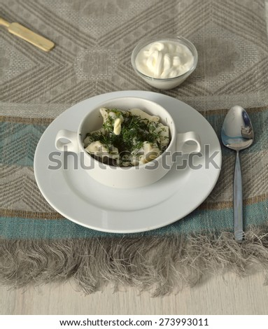 Hot pelmeni in a bowl with a piece of melted butter and sour cream  - stock photo