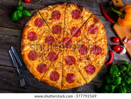 Hot pepperoni pizza and fresh vegetables on old wooden table - stock photo