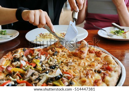 Hot pizza slice with melting cheese on a rustic wooden table. woman hand cut and slice pizza on wood table,