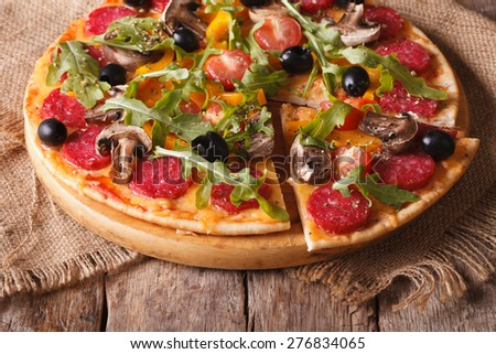 Hot pizza with arugula, salami and vegetables Close-up on the table. horizontal, rustic style  - stock photo