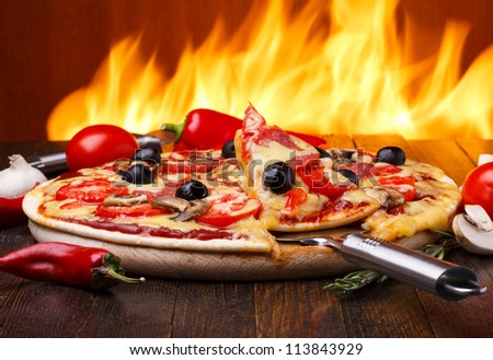 Hot pizza with oven fire on background - stock photo