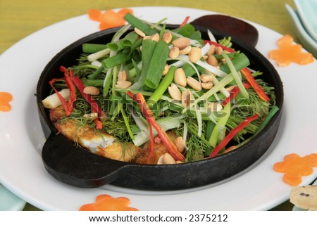 Hot-plate sizzled fish with aromatic herb vegetables and baked crackers