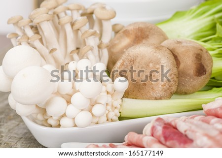 Hot Pot Ingredients - Thinly sliced beef, prawns, mushrooms, tofu puff and green leaf vegetables. - stock photo