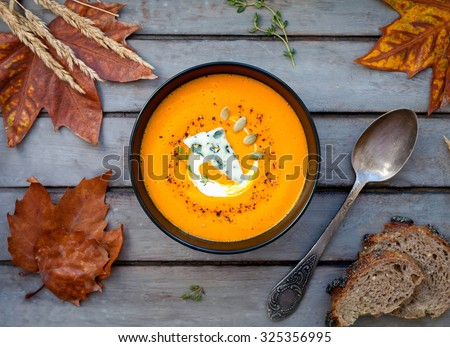 Hot pumpkin soup with blue cheese, herbs and multi-cereal bread on a wooden table. View from above - stock photo