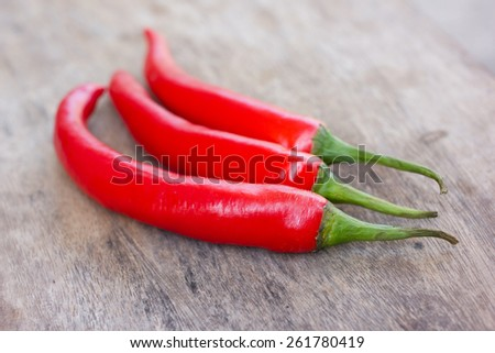 Hot red chili or chilli peppers over wooden background - stock photo