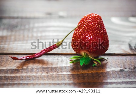 hot red chili pepper with strawberries on old wooden background. The concept of novelty and unexpected combinations of flavors - stock photo