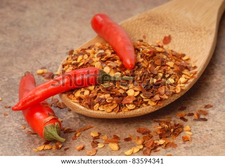 Hot red chili peppers and red pepper flakes on a wooden spoon - stock photo