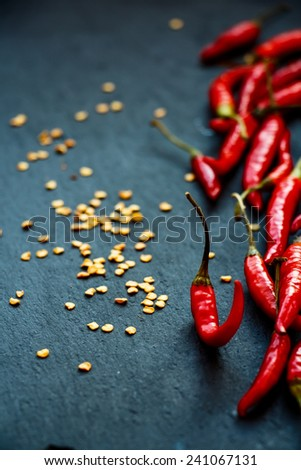 Hot Red Chili Peppers over dark grey background. Selective focus. - stock photo