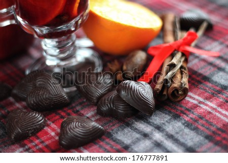 Hot red mulled wine with fruits and cinnamon on checkered tablecloth - stock photo