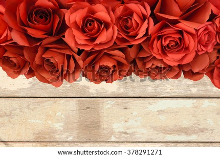 hot red paper rose on old wooden background