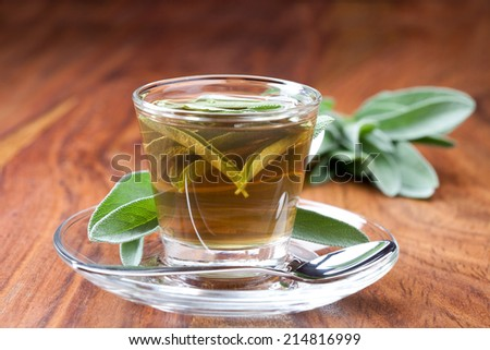 hot sage tea with fresh sage, silver spoon, wooden floor,  - stock photo