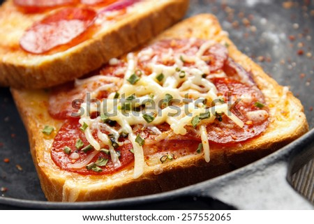 Hot sandwiches with pepperoni and cheese on frying pan closeup - stock photo
