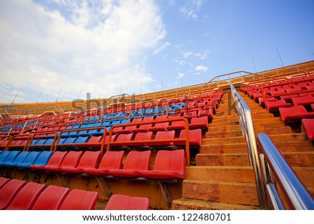 hot seats, red  and blue seats on stadium steps bleacher up bright sky