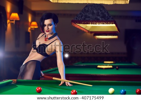 Hot sexy young woman at billiards club playing snooker - stock photo