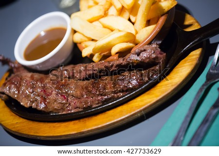 Hot Spanish carne en adobo - meat served with fried potatoes  - stock photo