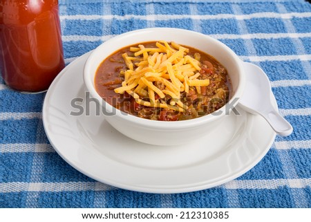 Hot, spicy chili in a white bowl with a spoon and bottle of hot sauce - stock photo