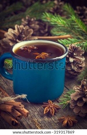 Hot spicy tea with anise and cinnamon in vintage blue enamel mug , selective focus, toned