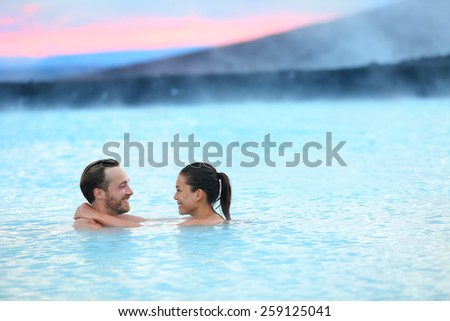 Hot spring geothermal spa on Iceland. Romantic couple in love relaxing in hot pool on Iceland. Young woman and man enjoying bathing relaxed in a blue water lagoon Icelandic tourist attraction. Sunset. - stock photo