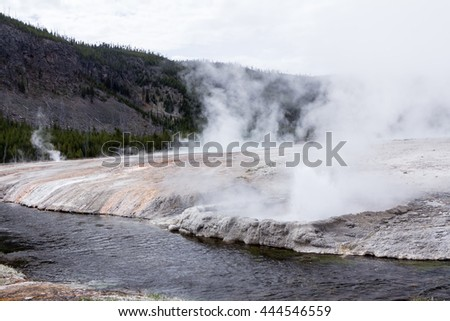 Hot springs near by a river in Midway Geyser Basin, Yellowstone National Park - stock photo