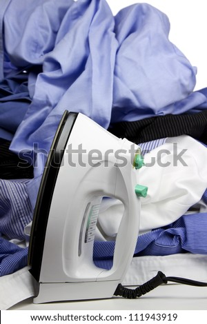 Hot steam iron with a pile of wrinkled clothing with selective focus on iron. - stock photo