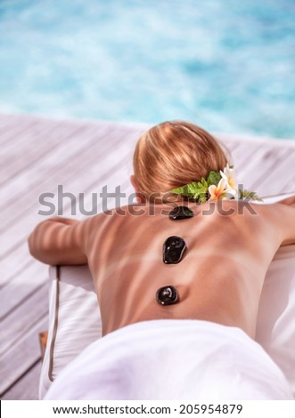 Hot stone massage on luxury spa resort on the beach, young beautiful woman lying down outdoors and enjoying dayspa, summer vacation concept - stock photo