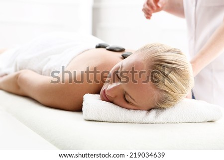Hot stone massage, Swedish massage .Attractive blonde woman in the office spa, relax with a massage  - stock photo