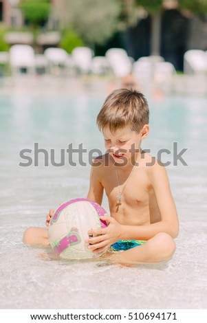 hot summer day a cute little boy playing with a ball in the water