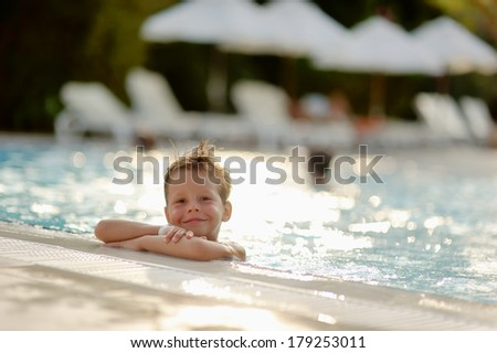 hot summer day, the boy fun dives and swims in the pool - stock photo