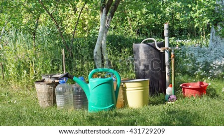 Hot summer - farmers and summer residents gather water for watering of plants in buckets and canisters. - stock photo