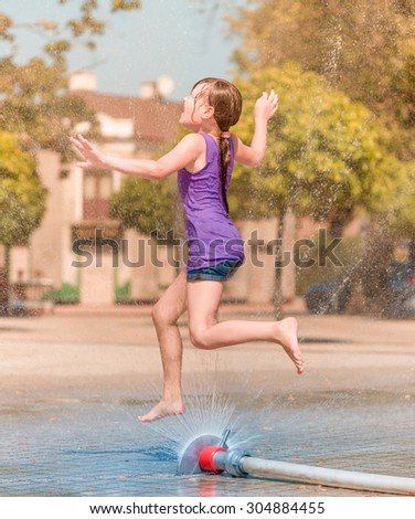 Hot summer in the city - girl is enjoying fountain with cold water - stock photo
