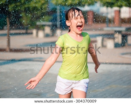 Hot summer in the city - girl is ruining through fountains - stock photo
