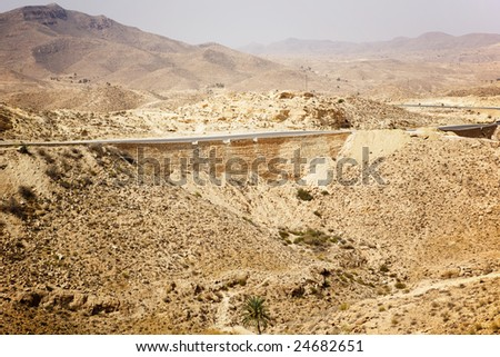 Hot summer sahara desert with one road only - stock photo