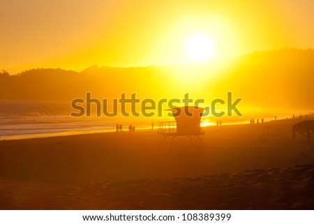 Hot summer sun setting over the horizon over a tranquil, beautiful shoreline scene. A lifeguard hut and silhouettes of people strolling along the beach complete this artistic, surreal scene. - stock photo