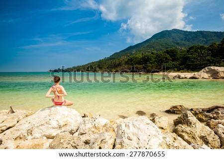 Hot summer yoga session on a beach - tropical Koh Phangan island, Thailand. Meditation - lotus pose - padma asana - stock photo
