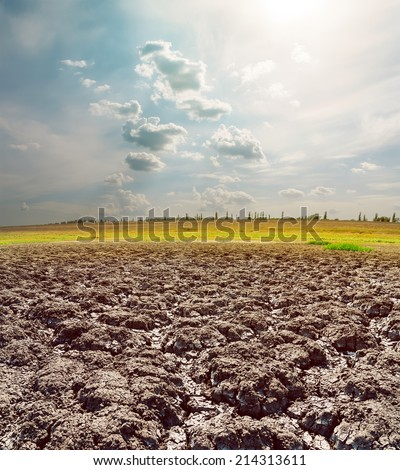 hot sun in clouds over cracked earth - stock photo