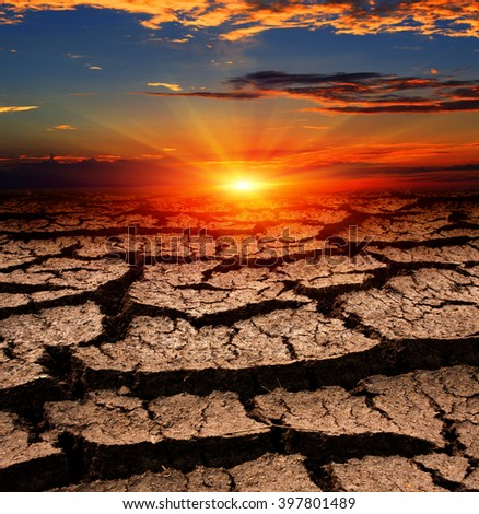 Hot sunset over cracked earth surface - stock photo