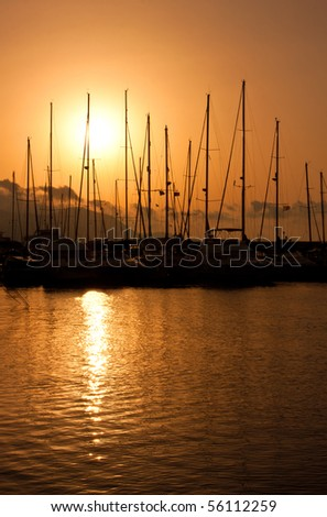 Hot sunset over marina with boats - stock photo