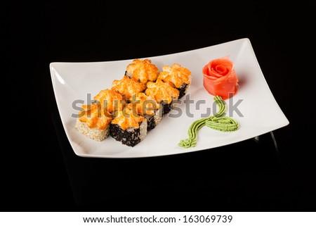hot sushi rolls on a black background - stock photo