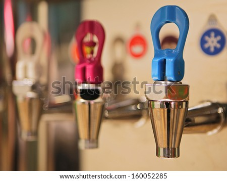 Hot tap, hot water and cold water to drinks on the same machine. - stock photo