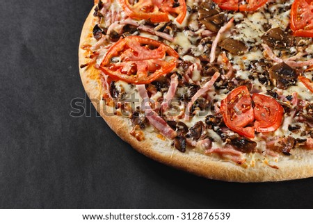 hot tasty delicious rustic homemade american pizza with mushrooms with thick crust on black table - stock photo