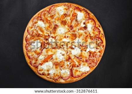 Hot tasty delicious rustic homemade american pizza with salami hamon mozzarella witj thick crust on black table - stock photo