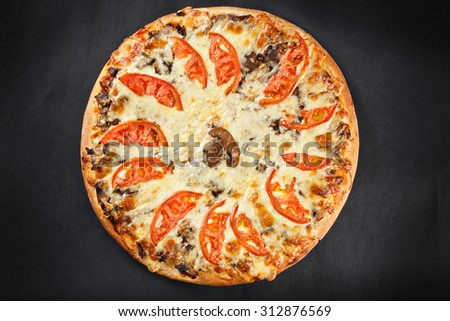 hot tasty delicious rustic homemade american pizza with tomato cheese mushrooms with thick crust on black table - stock photo