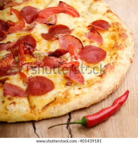 hot tasty  italian pizza with ham, pepperoni, mozzarella, cheese and basil leaves - stock photo