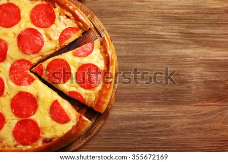 Hot tasty pizza with salami on wooden background - stock photo