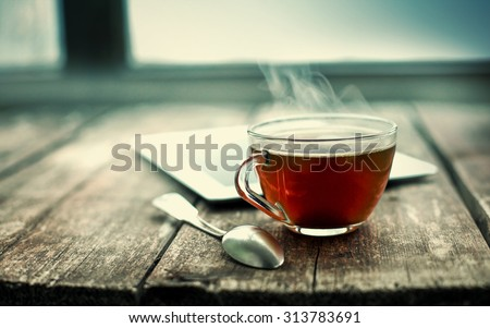 Hot tea cup on a frosty winter day window background - stock photo