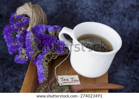 hot tea cup with tea on wooden spoon on wooden board - stock photo