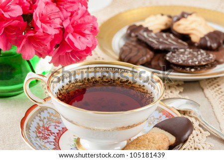 Hot tea in a vintage teacup on a lace tablecloth accented with cookies and bright pink Azaleas - stock photo