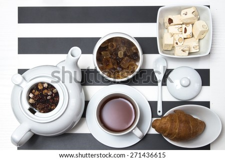 hot tea in the cup, tea brew in teapot with lid and spoon, sugar and caramel dessert with marshmallows and a croissant in a porcelain dish on a black and white striped table, top view - stock photo